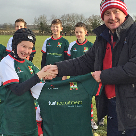 Murray West shaking hands with young rugby player holding up rugby shirt with Fuel Recruitment sponsorship logo on