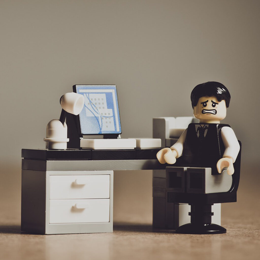 Lego style figure at a desk looking stressed and worried