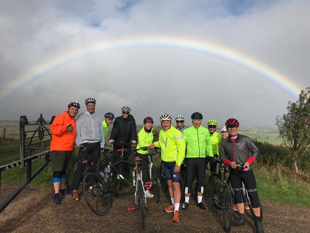 Members of Fuel recruitment team taking part in a coast to coast charity cycle ride under a rainbow