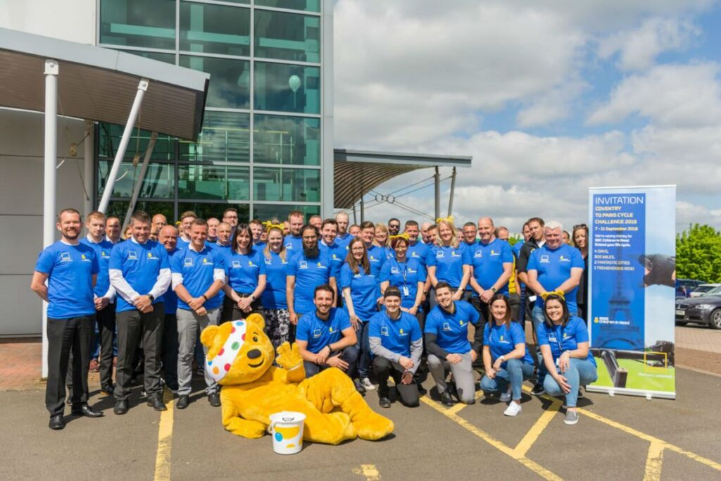 Group shot of people taking part in charity cycle ride for Children in Need with Pudsey Bear