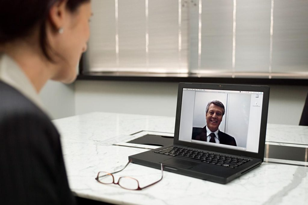 Business woman conducting remote interview on laptop